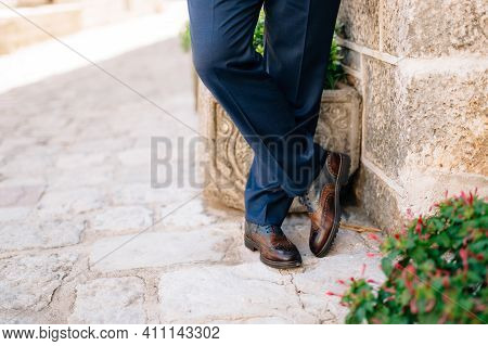 A Man In Blue Trousers And Leather Shoes Stands Cross-legged Against The Wall, Close-up