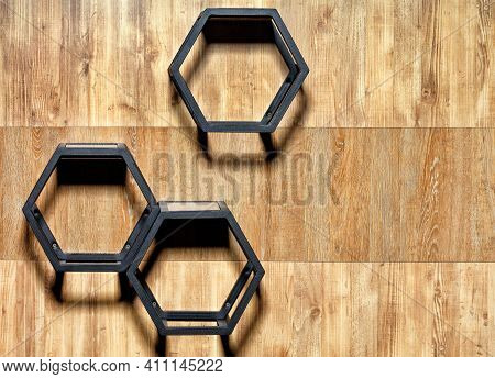 Metal Black Cubic Stylish Shelves With Hex Cutouts On A Wooden Wall Background, Copy Space.