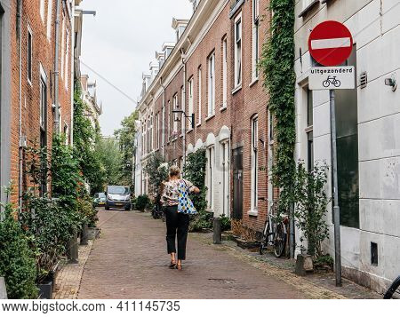 Haarlem, The Netherlands - Jul 21, 2018: Dutch Street Scene With Local Woman Walking Near The Tiny H
