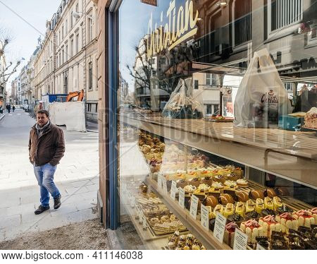 Strasbourg, France - Feb 23, 2019: Adult Male Walking On The Street With Multiple Pastries Sweets In