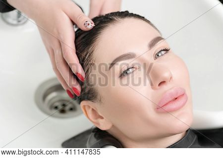 Hairdressers Hands Wash Long Hair Of Beautiful Brunette Woman With Shampoo In Special Sink For Shamp