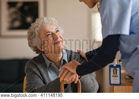 Smiling senior woman talking to her general practitioner visiting her at home during virus epidemic. Happy old patient holding hands of caregiver at nursing home and talking. Reassurance and console.