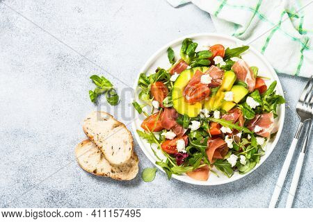 Green Salad With Avocado, Salad Leaves, Jamon Serrano And Tomatoes. Healthy Diet Lunch. Top View At