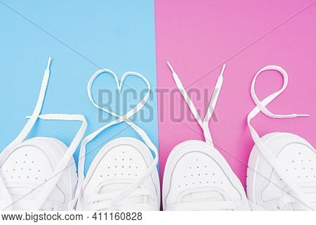 Matching White Sneakers With The Lettering Love Made Of The Laces On A Contrast Blue And Pink Backgr
