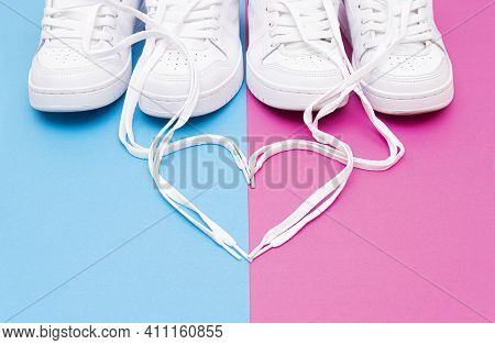 Crop View Of Matching White Sneakers And A Heart Symbol Made Of The Shoelaces On A Pink Blue Backgro