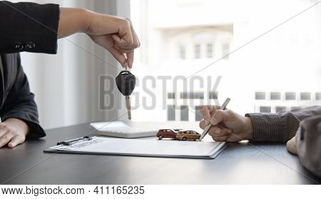 Female Attendant Handed Over The Rental Car Key To The Customer Who Signed The Contract And The Term