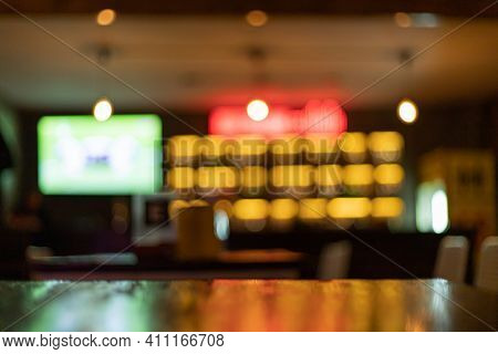 Image is blurred in a bar or tavern. Abstract image of an alcoholic beverage shop or pub. Colorful l