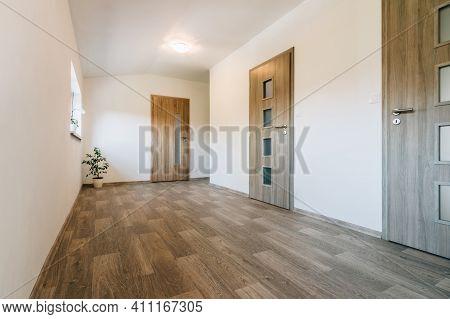 Hallway With Various Contemporary Room Door Designs, Wooden Floor And One Window. All Doors Have A W