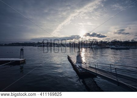 Harbor Pier In Winter At Dawn. There Is A Sailing Boat And An Island Park With Fallen Trees And Snow