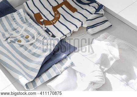 Folded Baby Clothes In A Dresser. Pregnancy. Child Planning. Awaiting. Birth Of Children