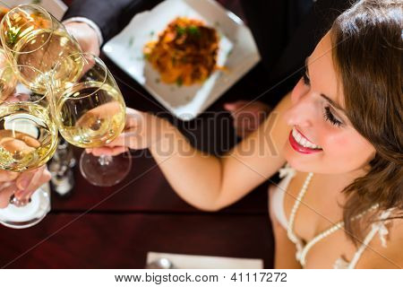 Good friends for dinner or lunch in a fine restaurant, clinking glasses