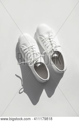 White Womens Leather Sneakers With Sun Shadows On White Background Top View. Stylish Youth Sneakers,