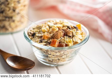 Beakfast cereals in bowl. Healthy muesli with oat flakes, nuts and raisins on white table.