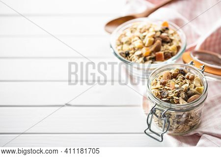 Beakfast cereals in jar. Healthy muesli with oat flakes, nuts and raisins