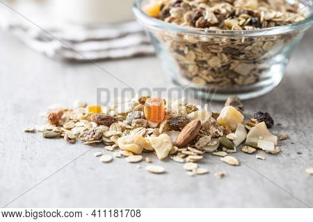 Beakfast cereals on kitchen table. Healthy muesli with oat flakes, nuts and raisins