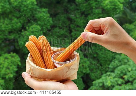Hand Dipping A Stick Of Delectable Churro In Caramel Sauce