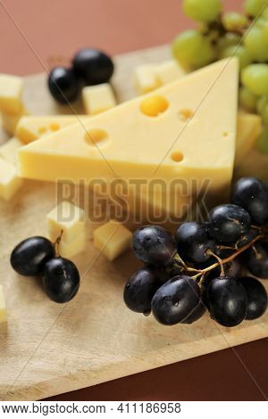 Maasdamer Cheese. Piece Of Cheese Maasdam Or Maasdamer, Green And Black Grapes On Wooden Board On Br