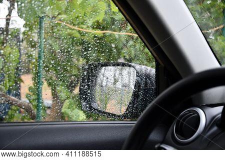 Wet Car Window Shot From Inside Automobile Near Defocus Driver Steering Wheel. Rainy Weather Car Tri