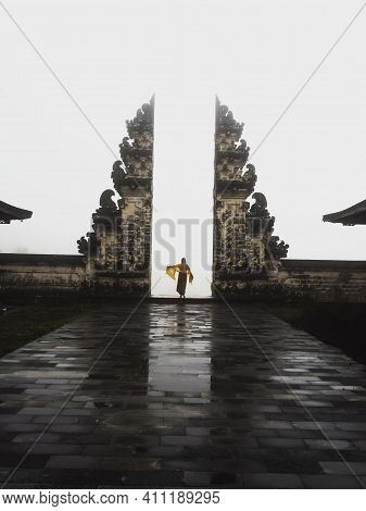 Natural Mirror Reflection Of Young Blond Woman Tourist Standing At Famous Gate Balinese Gateway To H