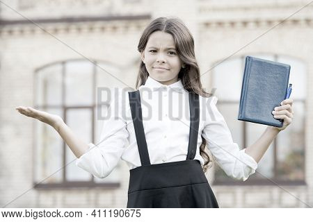 Ups. Education Is Compulsory. Little Child Make Helpless Gesture With Hands Outdoor. Small Girl Got