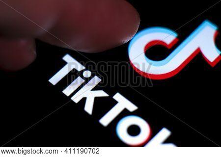 Madrid, Spain- March 5, 2021: Finger Pressing Tik Tok Logo On Black Screen In Mobile Phone