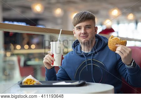 Content And Happy, Young Guy Eats On A Food Court, Fast Food. The Man Eats A Keeps Burger And Drinks