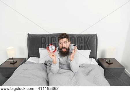 Need More Sleep. Tips For Waking Up Early. Man Bearded Sleepy Face Bed With Alarm Clock In Bed. What