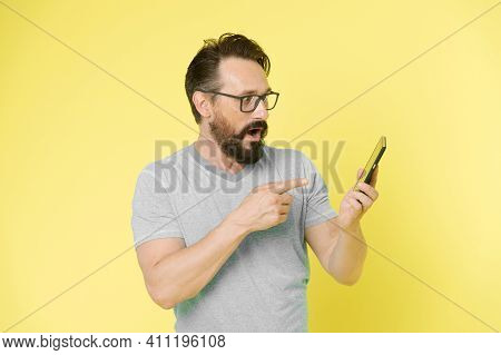 Guy Eyeglasses Cheerful Pointing At Smartphone. Man Happy User Interact Application For Smartphone.