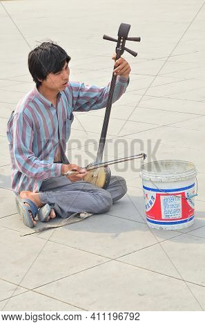 Beijing, China-may 26,2013: A Beggar Playing The Erhu, Chinese Traditional Instrument, By The Street