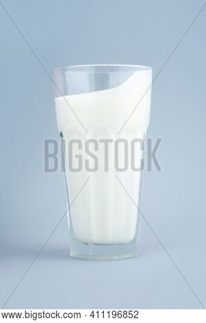 Probiotic Drink, Buttermilk Or Yogurt. Kefir In A Tall Faceted Glass On Minimalistic Blue Background