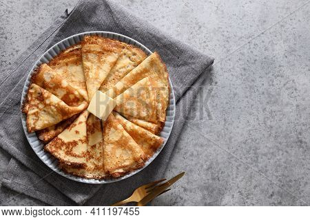 Russian Thin Pancakes Or Blini With Butter On Grey Stone Table. Top View. Shrovetide. Space For Text