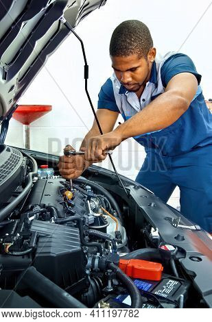 Horizontal Shot Of An Automotive Technician Working On A Car Engine.  This Is A Revised Picture.