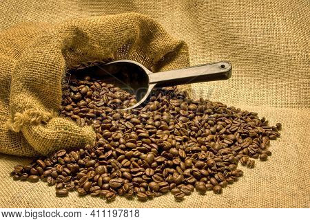 Horizontal Shot Of An Open Bag Of Coffee Beans On Its Side.  The Beans Are Pouring Out Of The Bag Wi
