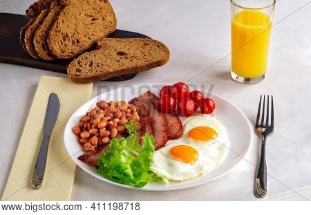 Hearty Breakfast With Scrambled Eggs, Bacon, Beans, Cherry Tomatoes, Homemade Bread, Orange Juice On