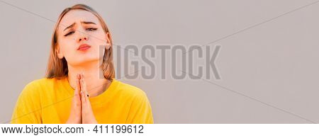 Please, I'm Begging. Portrait Of Woman In Yellow Sweetshot Praying And Asking Heartily, Feeling Desp