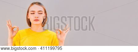 People, Peace And Meditation Concept. Calm Young Woman Practices Yoga Indoor, Shows Okay Sign With B