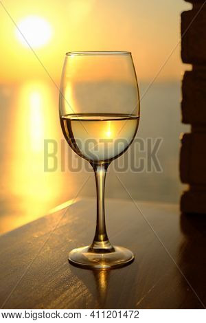 Glass Of White Wine On Colorful Sunset Background. Reflection Of The Sun And Sea. The Concept Of Rom