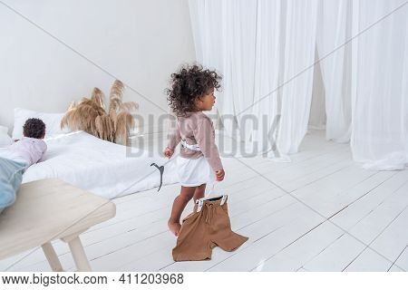 Little Curly-haired African American Girl Plays, Runs By The White Bed, Has Fun, Laughs, Smiles. The