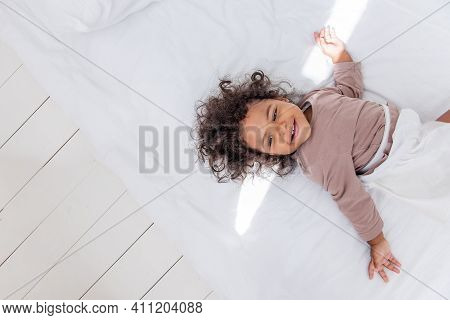 Little Curly African American Girl Lies On A White Bed, Has Fun, Laughs, Smiles, Plays. The Concept