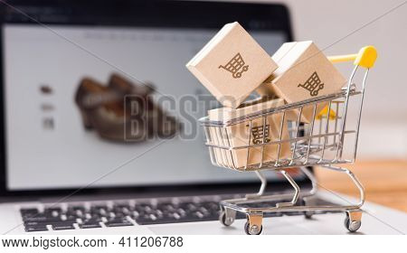 Online Shopping - Paper Cartons Or Parcel With A Shopping Cart Logo And Small Cart On A Laptop Keybo