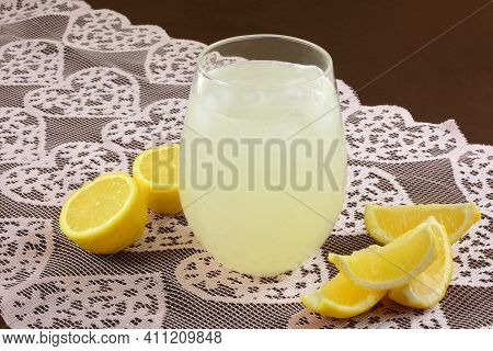 Drinking Glass Of Lemonade With Lemon Wedges And Lemon Haves On Lace Heart Table Runner O Brown Tabl