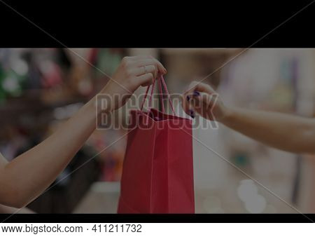 Shopping bag given to female customer by female shop assistant and black stripes with copy space. retail and shopping concept digitally generated image.
