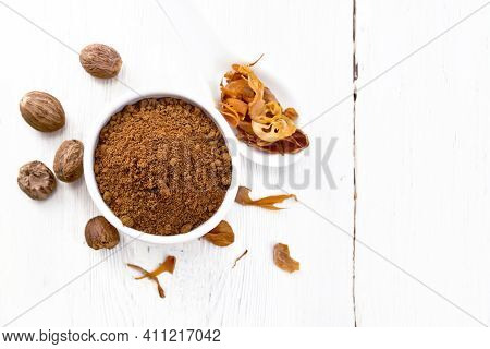 Nutmeg Round In Bowl And Mace In Spoon On Light Board Top