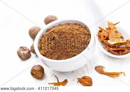 Nutmeg Round In Bowl And Mace In Spoon On White Board