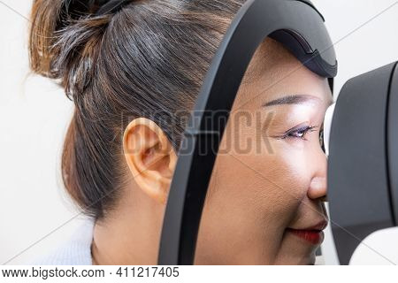 Elder Asian Women At The Optometry Equipment. While Optometrist Using Subjective Refraction To  Exam