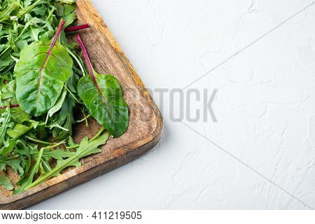 Herb Green Salad With Arugula And Mangold, Swiss Chard Set, On White Stone  Background, With Copy Sp