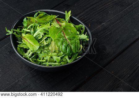 Fresh Raw Mixed Greens Arugula Raab, Mangold, Swiss Chard Set, On Black Wooden Table Background, Wit