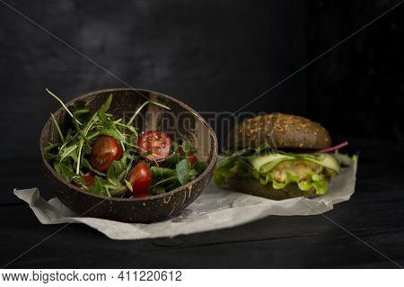 Fish Burger Arugula And Salad With Tomatoes And Arugula On Dark Wooden Board.