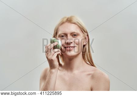 Smiling Young Caucasian Man With Long Blond Hair Washing His Face With Sponge And Foam While Posing