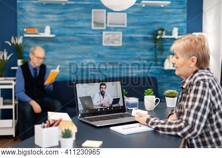 Young Doctor Talking With Senior Patient During Facetime Consultation. Elderly Telemedicine Online C